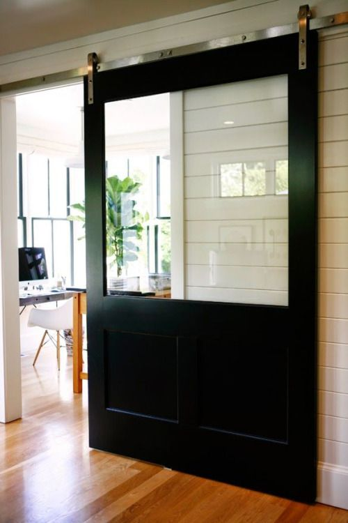 A new twist on the barn door. A glass panel lets light shine through the house.
