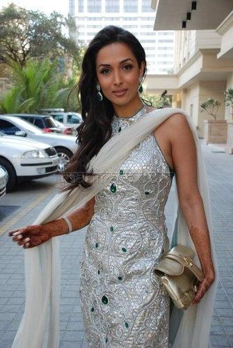 Maalika Arora in a beautiful ivory brocade print dress with emerald jems.