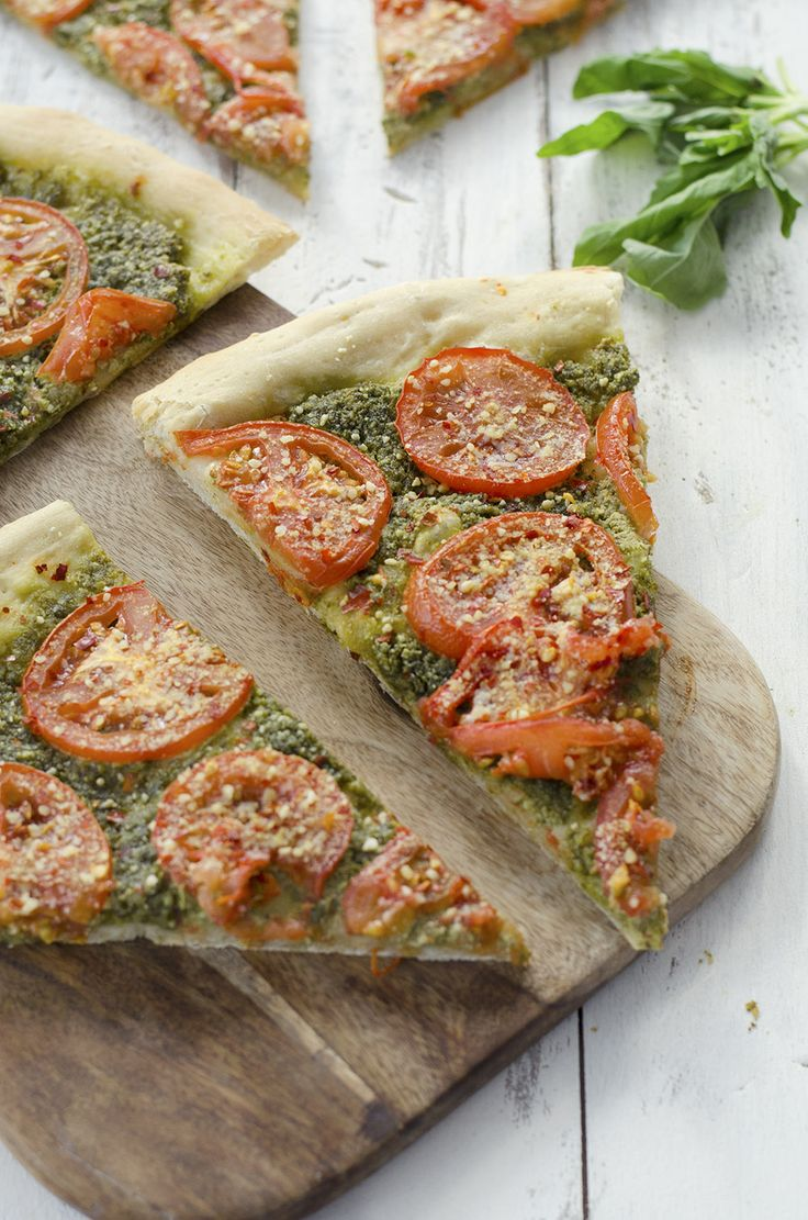 Vegan Pesto Pizza! You'll never guess this pizza was dairy-free! Pumpkin seed pesto topped with sliced tomatoes then roasted to perfection and topped with homemade vegan parmesan cheese! You've gotta try this pizza, even omnivores loved this one. www.de