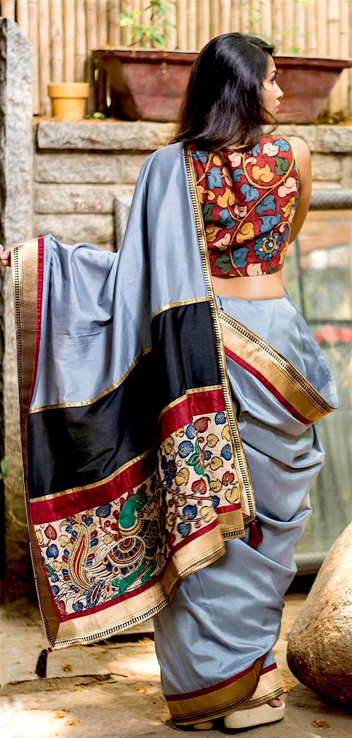 semi-silk saree in grey with a black-gold brocade border and rich Kalamkari work.
