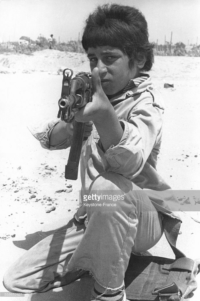 Sur une plage mediterraneenne situee pres du port de Tyr, dans le sud Liban, ce garcon tient un pistolet mitrailleur sovietique kalachnikov et fait partie des plus jeunes recrues de l'OLP (Organisation de liberation de la Palestine) qui s'entrainent la avant de rejoindre les rangs des Feddayines qui poursuivent plus que jamais leur lutte dans cette region du Proche-Orient, le 2 aout 1978 au Liban.