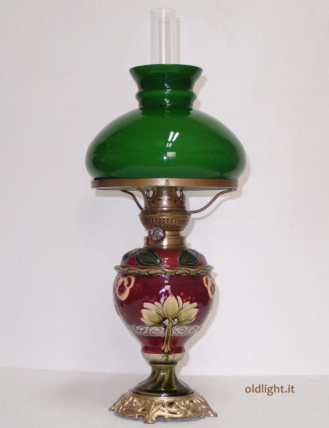 Bellissima lampada  in maiolica, base in metallo dorato, origine tedesca primi 900, assolutamente autentica; Bruciatore Kosmos  14''' originale antico;  Patralume in vetro opaline verde con interno bianco; Tubo vetro soffiato Kosmos 14'' ( originale  )