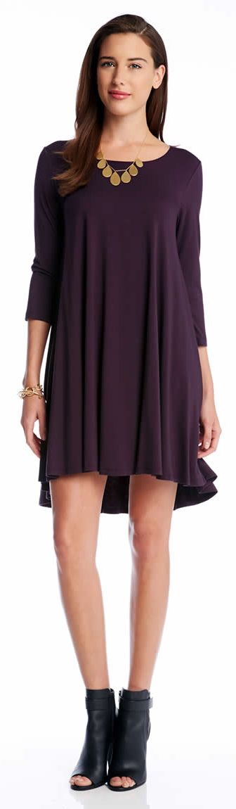 Shaped from soft stretch-knit jersey fabric, this 3/4 sleeve dress goes in full swing with a voluminous trapeze silhouette in a solid eggplant purple color.