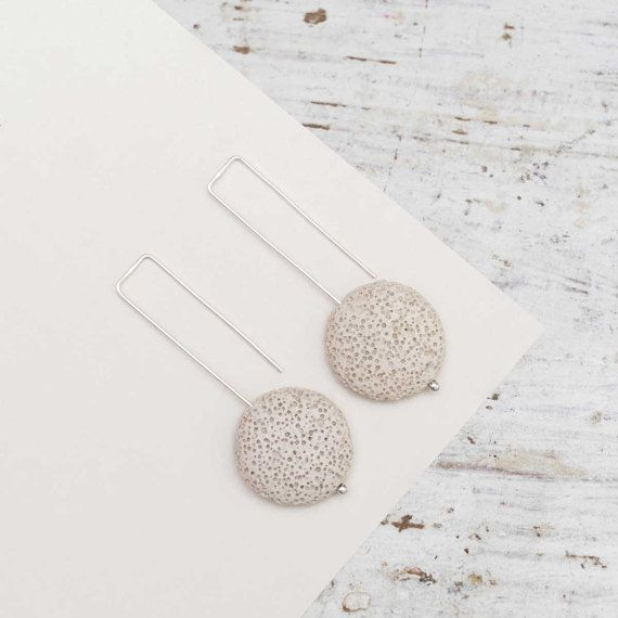 Earrings Grey Moon is a minimalist interpretation of the Full Moon in cloudy night sky Silver, Moon and water form a chain with feminine energy and are a symbol of purity, femininity and maturity.  Earrings are made of sterling silver wire and grey lava stone. Earrings are wearable in two ways: the short or the long part in front.  Jewelry is made of recycled sterling silver Earrings length is about 60mm    Please note – this link will take you to our affiliate online shop where you can buy…