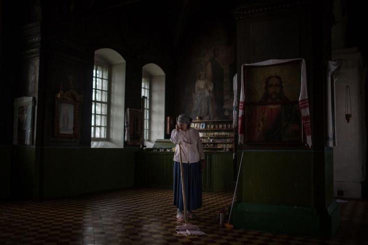 Zhanna Fedukova washes the floors of the old Pokrov church located in the village of Ust-Pechenga, on Sukhona River, where she lives.  Fedukova and her husband are the only people in the village trying to keep the church in proper conditions. It was abandoned for several years before their arrival. July 2015.