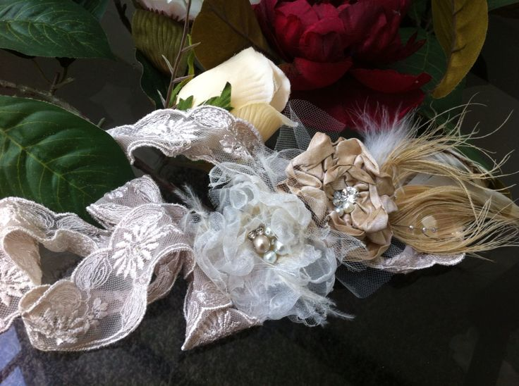 Champagne peacock feathers with a raw silk flower and organza flower. wwwmargotarderndesigns.com