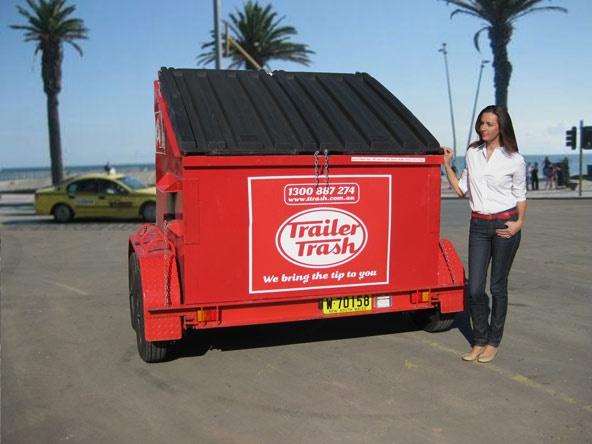 Woman standing next to a 4m Trailer Trash skip bin.