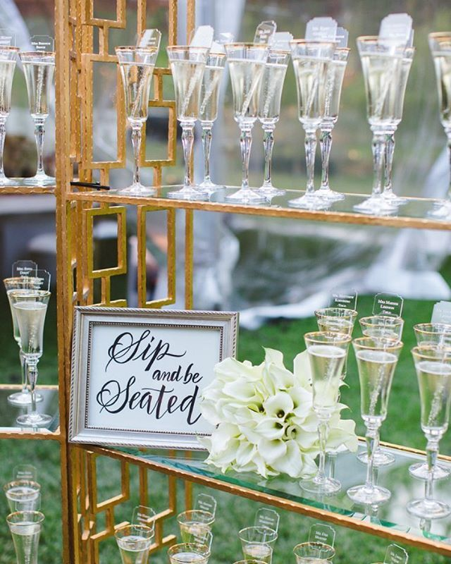 @wishlovesthis back again to share my beautiful first cousin's #wedding on #stylemepretty today! We decorated several beautiful gold bar backs with champagne flutes, candles, and floral arrangements and positioned them at the entrance of the reception tent. As guests arrived at the tent, they took their champagne flute with their name and table assignment etched on an acrylic stir stick! See more of @boobsandloubs' wedding on SMP now! | Photography: @closertolovefamily | Cinematography…