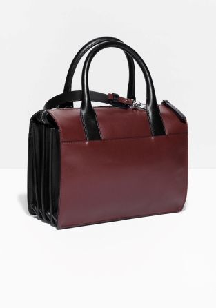 Compact yet capacious, this dapper leather handbag is detailed with pleats on sides. Designed for several styling options, it is furnished with a detachable shoulder strap.