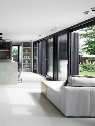 Oversize windows/sliding doors and chunky concrete kitchen bench/dining area.