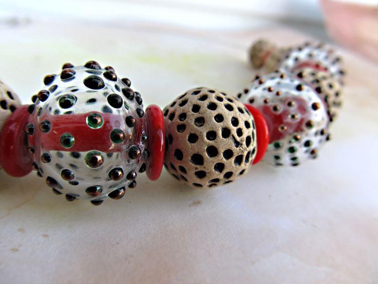 Červený+panter+Originální+masivní+náhrdelník+z+vinutého+skla+a+keramických+korálků+(vše+autorská+práce).+Hlavním+doplňkem+je+6+různě+velikých+keramických+korálků+a+3+duté+vinutky+o+velikosti+21+x+19+mm.+Obruč+v+barvě+stříbrné.+Zapínání+na+karabinku+s+prodlužovacím+řetízkem.+Použit+obecný+kov.