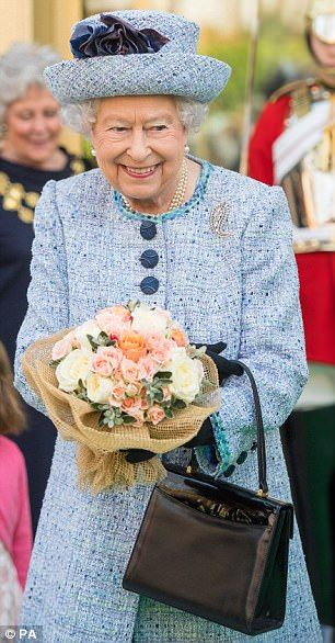 Elegant: The  monarch donned a powder blue tweed coat and matching hat for the occasion...