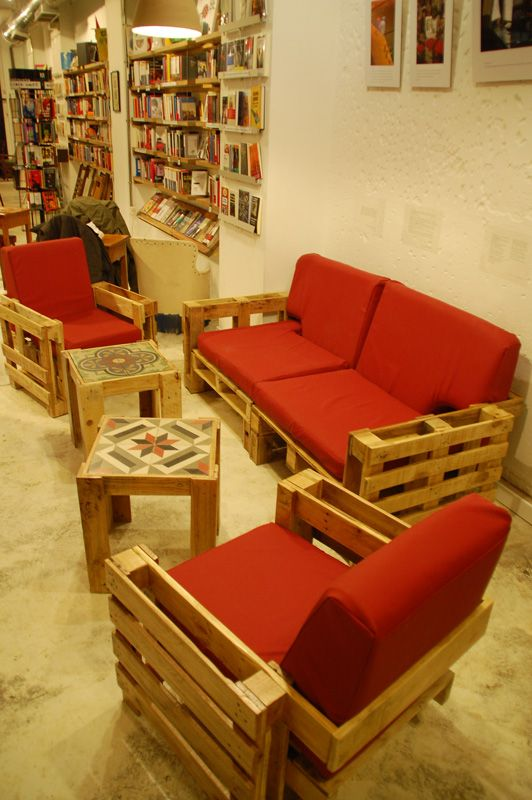 Pallets living : A friendly space where to read a book or a newspaper, drinking a beer or a coffe. Living room with recycled pallets made of a double sofa, two individual armchairs customized with glass holder and magazine racks, two tables with antique 1920′s glaze tile, two cardboard lamps. In Ubik Café Valencia.
