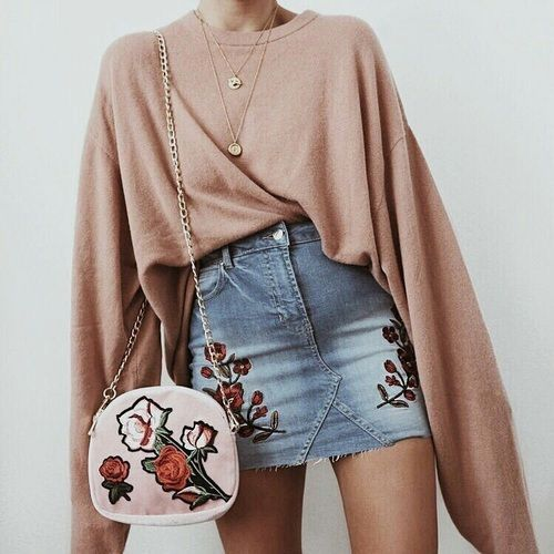 Beige oversized pullover tucked into a denim mini skirt with roses embroidered on them.