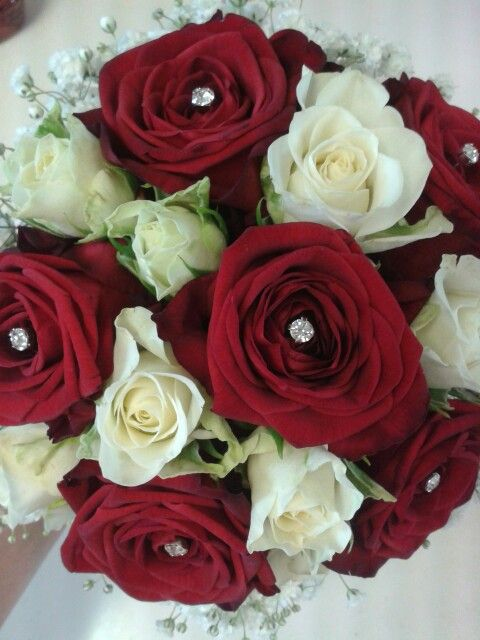 Bridal bouquet with red Naomi roses, and ivory Snowflake spray roses, edged with white gypsophila. Diamonte detailing has been added with pins.