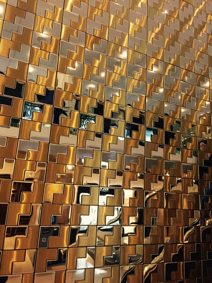Project 6, Atrium & riverwalk: glossy gold & silver tiles in a geometric pattern add interest to a feature wall