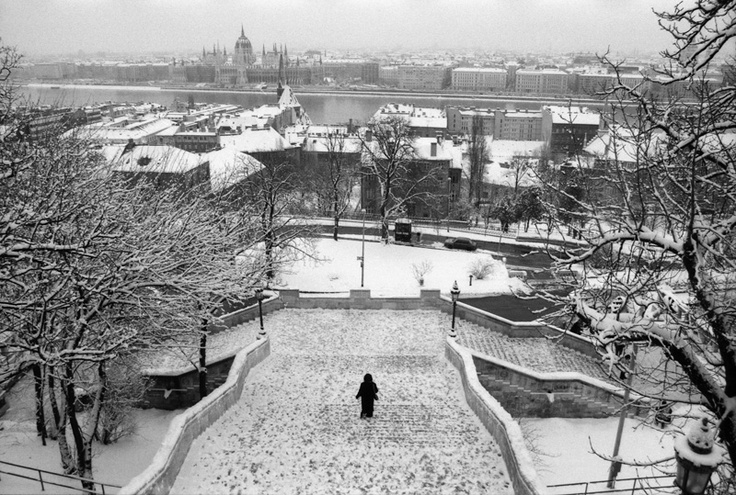 Winter: a lone figure walks from the Fishermans` bastion, the Danube and parliament in the distance.