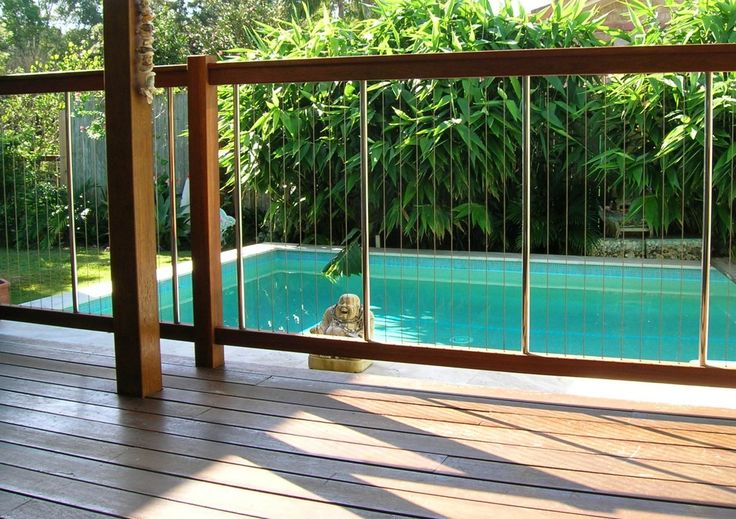 Enchanting Pool Fence Design Ideas With Modern Architecture With Brown Wooden Swimming Pool Fence And Wooden Swimming Deck Also Outdoor Furniture Plus Unique Statuary And Green Trees In Garden Ideas
