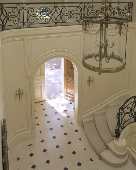 foyer in a French countryhouse....floors, ironwork, pendant, sconces, stairs, stunning!