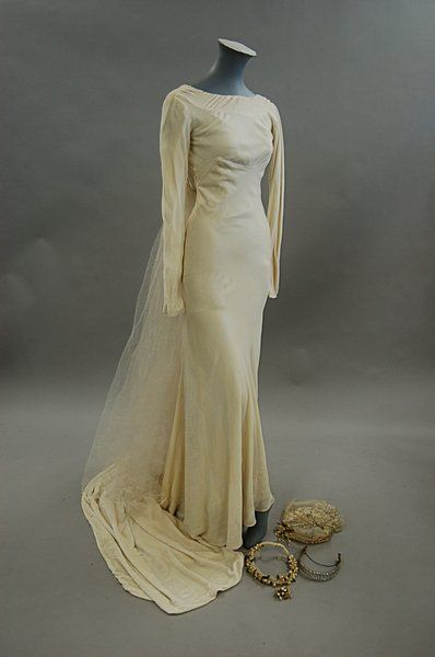 A Victor Stiebel ivory velvet bias-cut bridal gown, early 1930s, labelled 22 Bruton St, Berkeley Square, tel Mayfair 0048' and with handwritten tag `Miss Levy', the bodice cut high at the front and low at the back, buttons to narrow sleeves and back-fastening, very long trained skirt, with matching silk petticoat, bust 76cm, 30in, waist 61cm, 24in; a silk tulle veil and orange blossom headress; together with a 1934 wired bridal headress and a diamante headress.