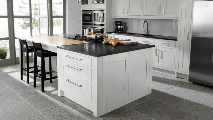 Cruachan Painted Blizzard White.  The bold white painted finish on this solid ash shaker 'in-frame' kitchen, along with the chunky end panels gives a very contemporary look to this kitchen.    The timber work top at the seating area on the island adds a touch of warmth and interest to the design.