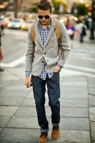 Men's Grey Wool Blazer, Navy and White Plaid Longsleeve Shirt, Brown Suede Desert Boots, Tan Backpack, and Navy Jeans