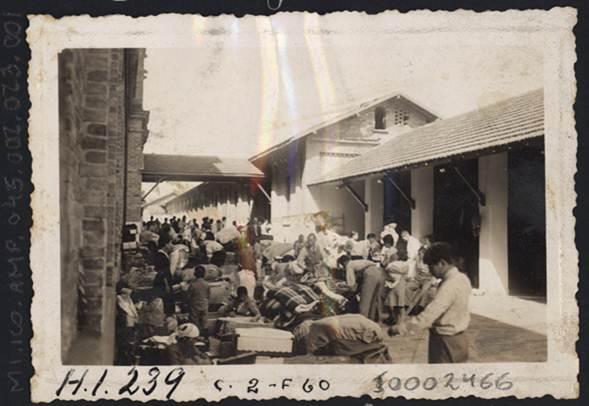 Imigrantes japoneses na área externa da Hospedaria do Brás abrindo suas bagagens para arejar e tomar sol, após o longo período de viagem de seu país de origem à São Paulo.