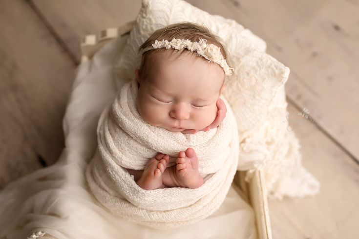 Newborn pose baby girl wrapped in cream with feet sticking out wearing cream floral headband And lying in white antique bed