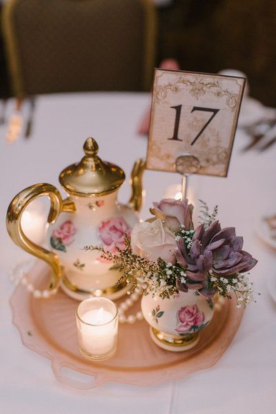 Vintage-inspired wedding centerpiece idea - votives, pearls, vintage tea pot and teacups holding ivory rose, succulent + baby's breath flower arrangements  {Karen Ann Photography}