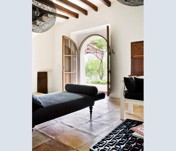 Il living, subito all'ingresso, presenta materiali chiari e tonalità neutre per moltiplicare la luce. Per il soffitto sono state restaurate le travi in legno originali della fattoria