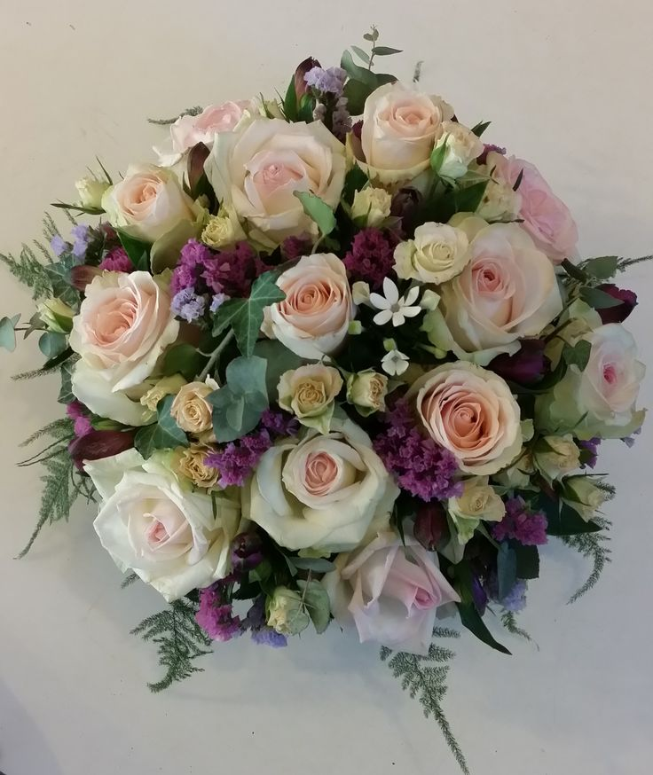 Composition piquée avec roses, roses branchues, lierre, statice, alstroemérias, asparagus. Tons rose pâle et mauve.