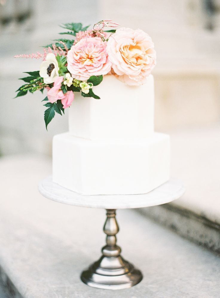 white hexagon shaped wedding cake. Love the silver cake stand and floral!