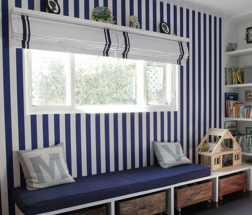 The rather high impact feature of the blue and white vertical striped wallpaper is attractively broken by the contrasting stripe width of the roman blind. #interiordesigns #romanblinds