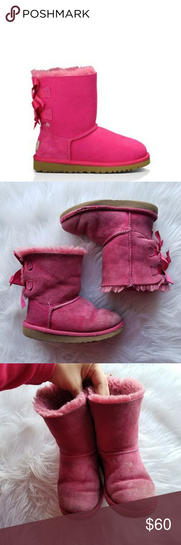 Ugg Bailey Bow Boot Cerise The Bailey Bow is embellished with fixed, double ribbon bows at the back, enhancing the defining features of an UGG® Classic. A light, flexible outsole and foundational Twinface sheepskin keep feet cozy and dry indoors or out, while durable construction and added foam ensure all-day comfort. Preloved, some tears and signs of wear as seen in the pictures. Still a long life left. Size 11 Toddler UGG Shoes Boots