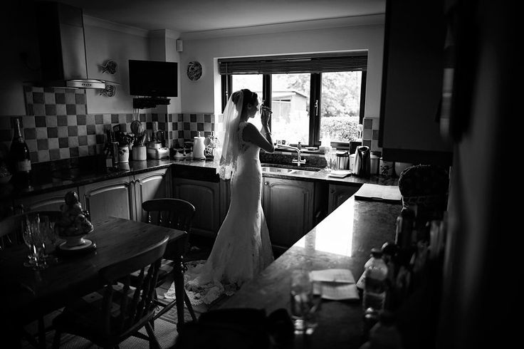 Black and white window lit portrait of a bride during quiet reflection