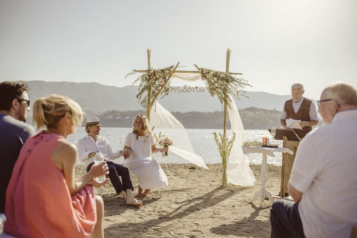 Ceremony on the beach, aisle made of bamboo with flower arrangements of olive branches and roses