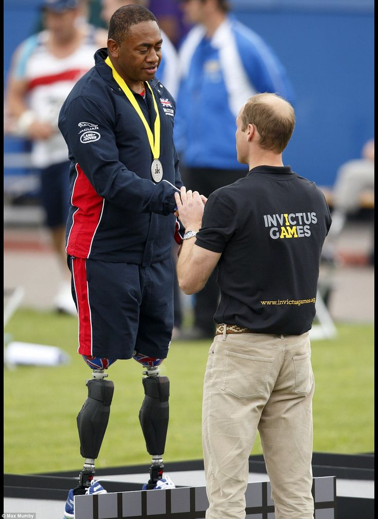 Prince William presents Team GB's Derek Derenalagi with his silver medal which he won in t...