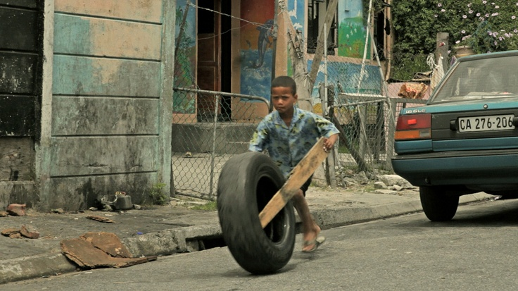 A little boy playing with a tyre in Cape Town streets.
