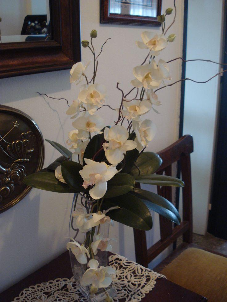 Largas varas de orquídea phalaenopsis con ramas de sauce eléctrico.