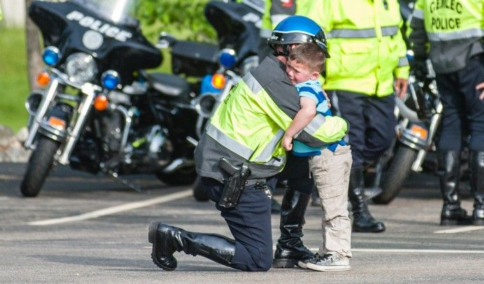 It's a photo that has been shared thousands of times online. A photo of a young boy almost limp in a police officer's arms outside Morin Funeral Home in Leciester, where the body of slain Auburn Police Officer Ron Tarentino Jr. was brought late Sunday afternoon, May 22.