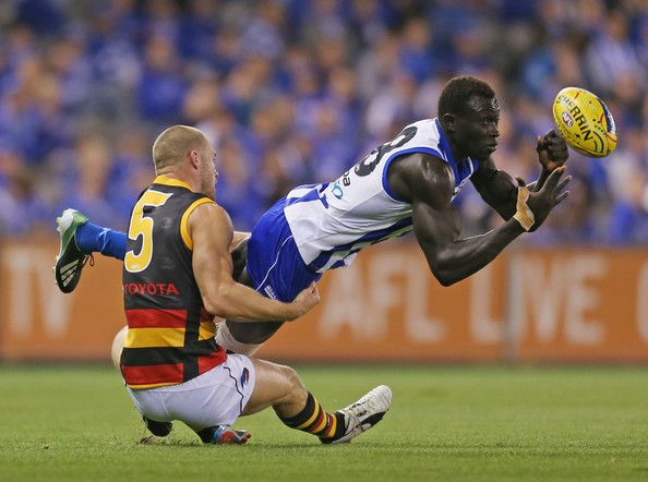 Majak Daw of the Kangaroos is tackled by Scott Thompson of the Crows during the round nine AFL match between the North Melbourne Kangaroos and the Adelaide Crows at Etihad Stadium on May 26, 2013 in Melbourne, Australia. (May 25, 2013 - Source: Scott Barbour/Getty Images AsiaPac)