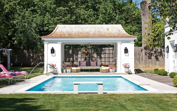 Open pool house with floor to ceiling glass windows finished with distressed style shingles.
