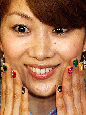 Japanese badminton player Reiko Shiota shows off her brightly coloured nail polish with depictions of both her country's and the host nation's flags. Her earrings give Britain the tie-breaker.