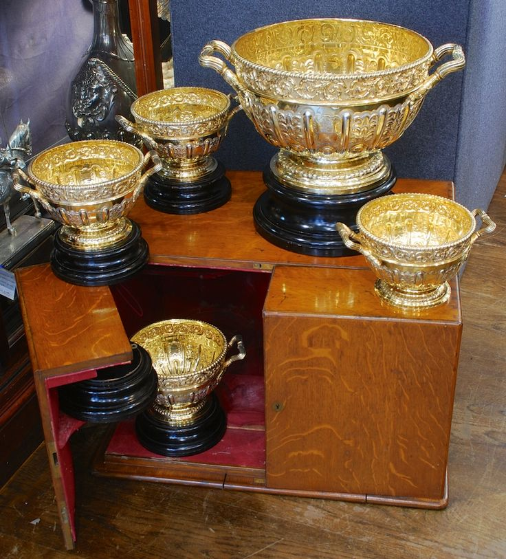 A suite of five Victorian silver-gilt punch bowls J B Carrington London & Birmingham 1893  with contemporary engraved crests & presentation inscription to the foot of the large bowl.  In original fitted wooden box  Large bowl: 12 1/2 inches (32cm) high on plinth, 17 inches (43cm) over the handles.  Four small bowls: 7 1/4 inches (18.5cm) high on plinth, 9 1/2 inches (24cm) over the handles