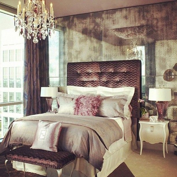 A pretty bedroom with what appears to be a smoky glass wall behind the bed.  Softly reflects the chandelier and other objects in the room.