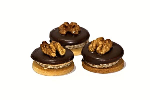 V troubě upečená kolečka z ořechového těsta slepená po dvou smetanovým krémem, zdobená čokoládovou polevou a ořechy.