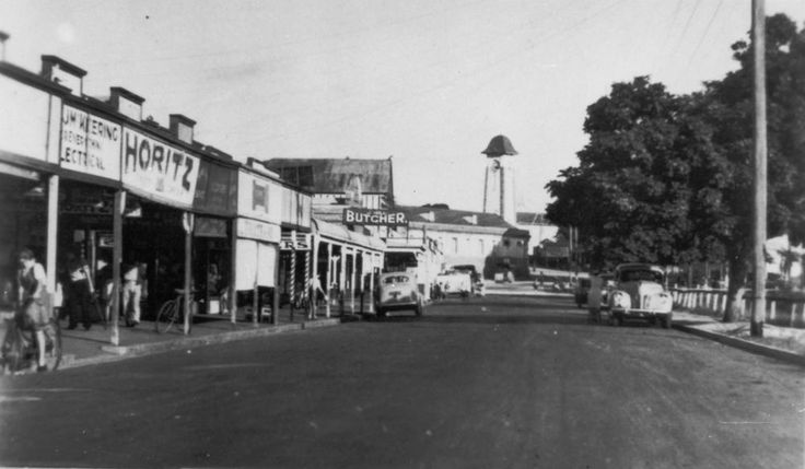 Looking down Brighton Rd, Sandgate, Brisbane, ca. 1930 - Looking down Brighton Rd towards the Sandgate Town Hall with clocktower. Shops line the street on the left and there is a park on the right.