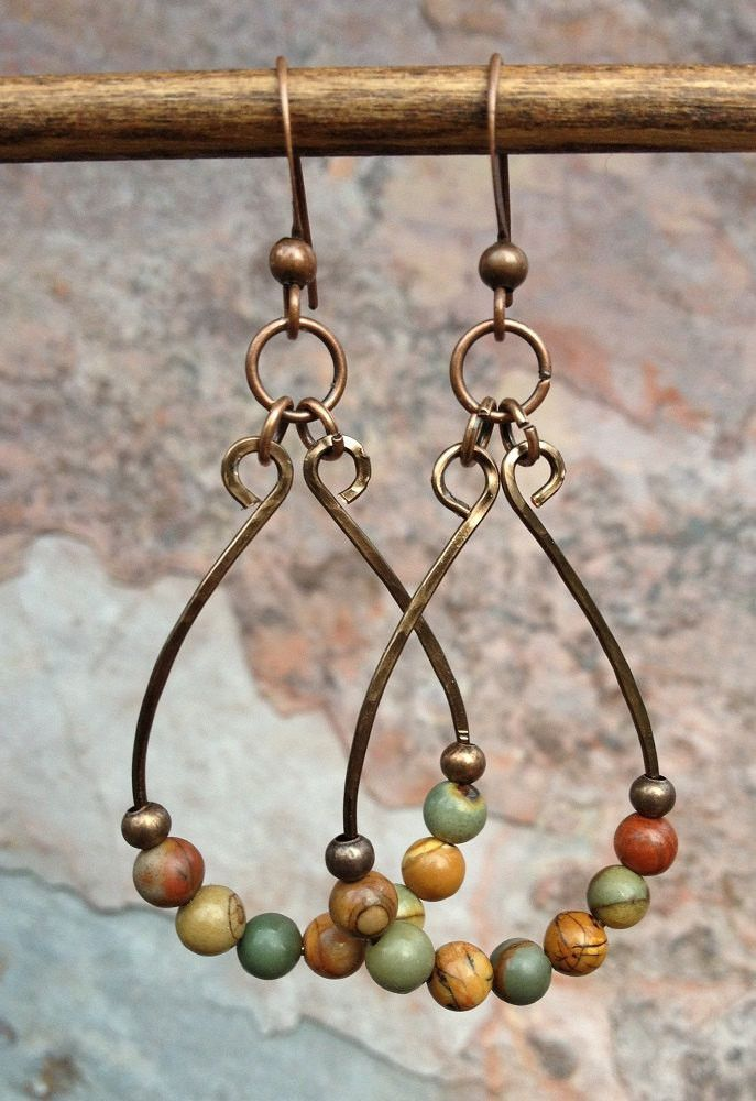 "A hammered copper teardrop with small red creek jasper stones. The colors of these earrings are very warm and rich. Approx. 2"" in length."