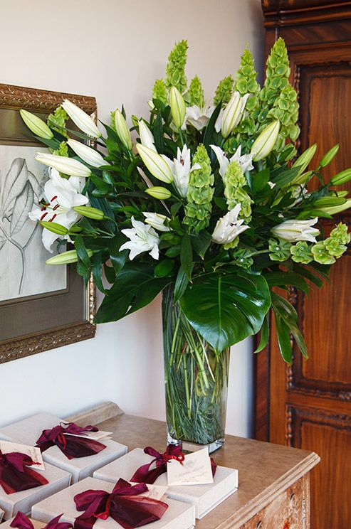 Monstera leaves and bells of Ireland are paired with white lilies.