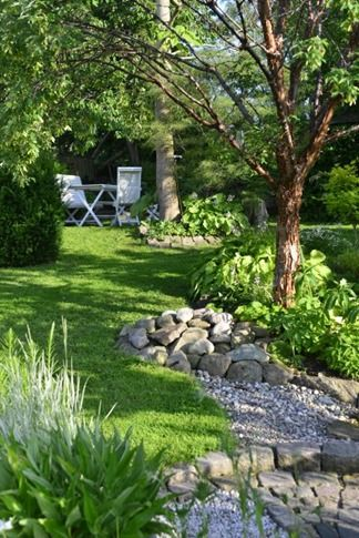 Use different size stone to remedy water drainage problems in uneven yard and funnel water to appropriate plants.